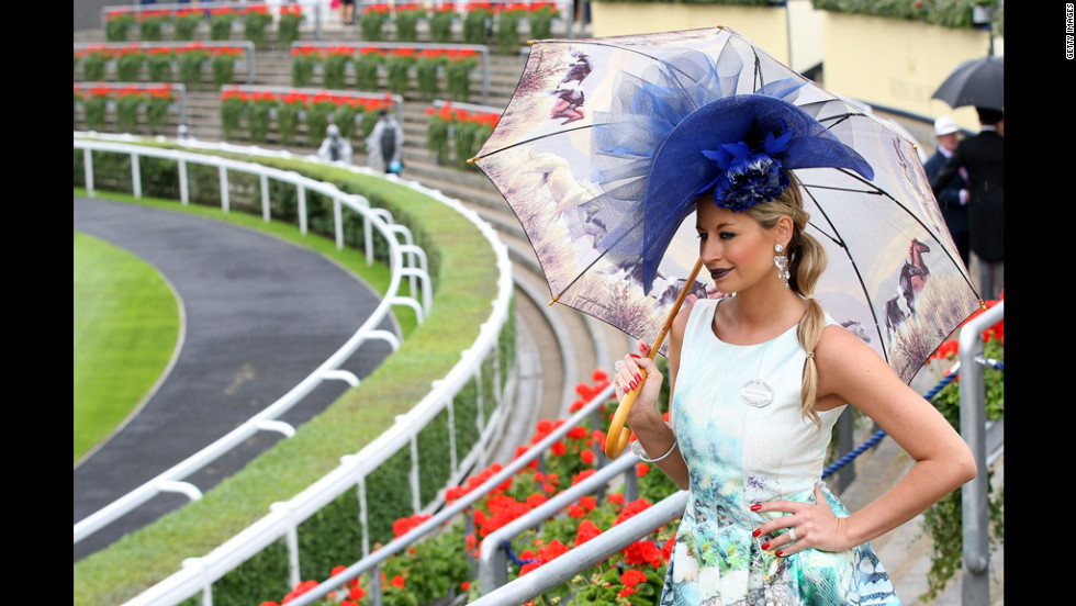 A woman poses with a striking hat and equine-themed umbrella.
