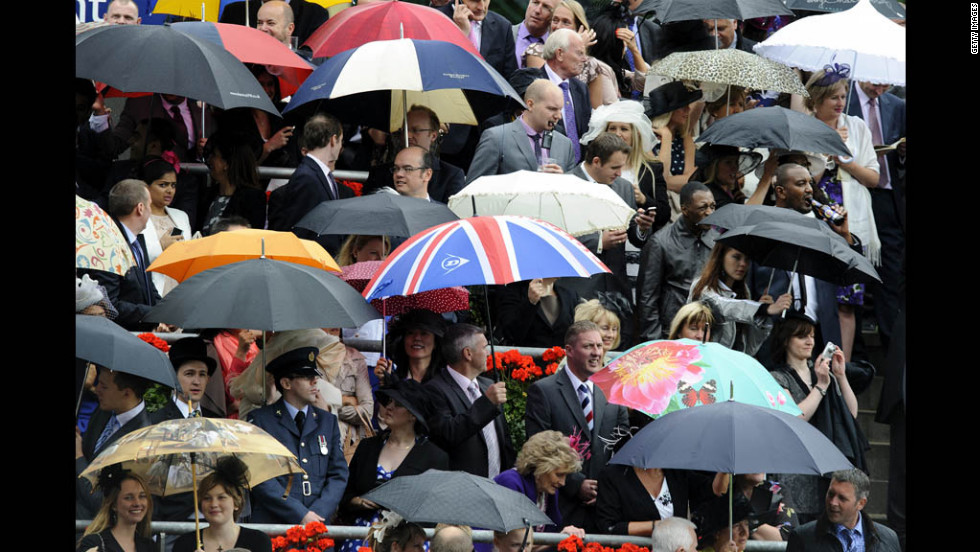 Attendees escape the rain under their umbrellas on day four.