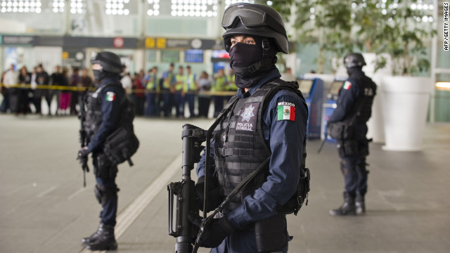 Federal police officers stand guard at Benito Juarez International Airport in Mexico City on Monday.