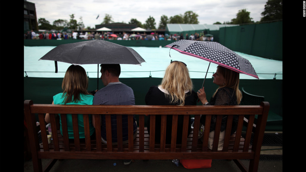 Spectators wait for play to resume after Tuesday's matches were halted due to rain June 26.