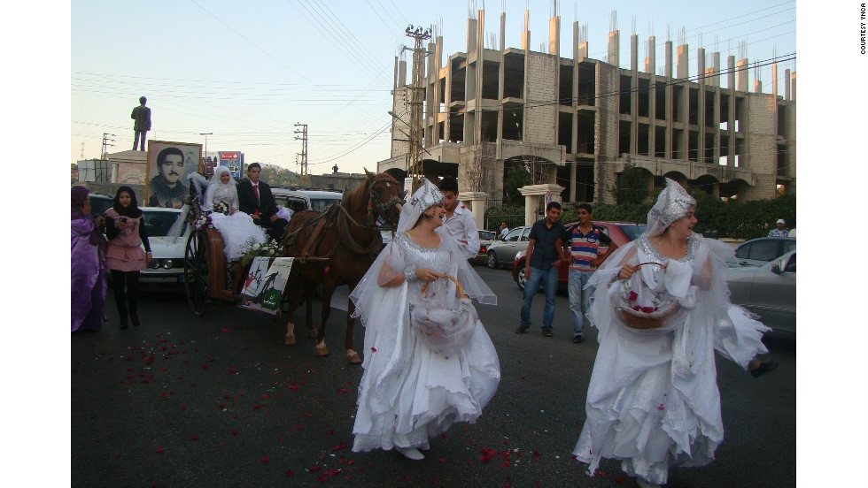 "Women dance in the street before a carriage bearing newlyweds affiliated with YNCA. The organization used the occasion to declare a ""week of joy,"" and encouraged people to celebrate by dancing in the street, defying prohibitions against such behavior that have arisen in recent years."