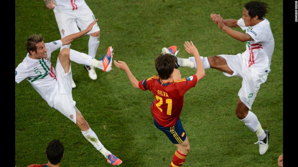 Spanish midfielder David Silva, in red, vies with Portuguese defender Fabio Coentrao, left and Portuguese defender Bruno Alves.