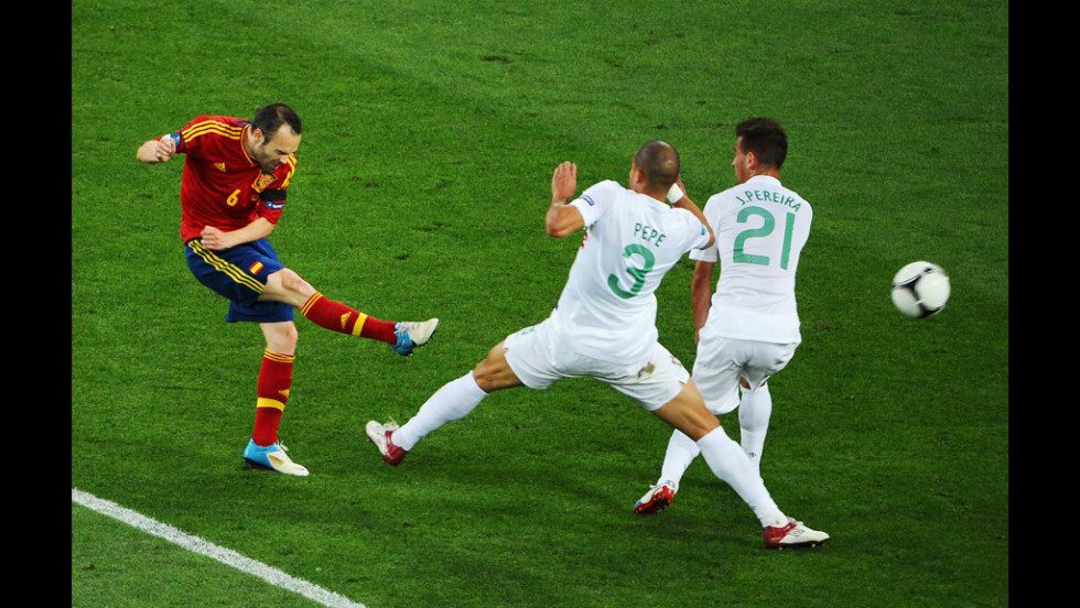 Andres Iniesta of Spain shoots past Pepe and Joao Pereira of Portugal.