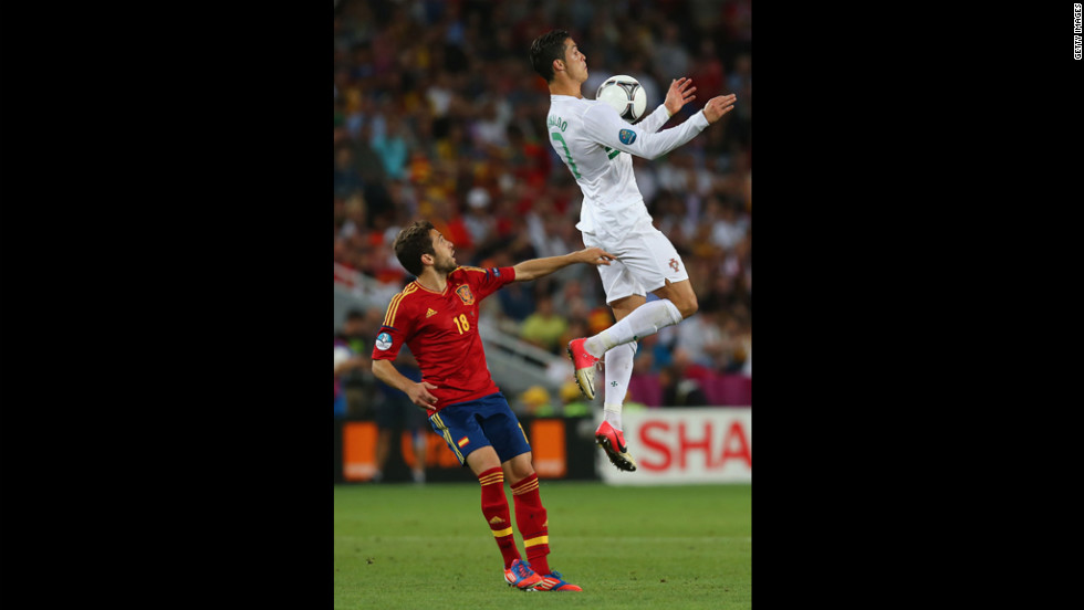 Cristiano Ronaldo of Portugal jumps for a high ball in front of Jordi Alba of Spain.
