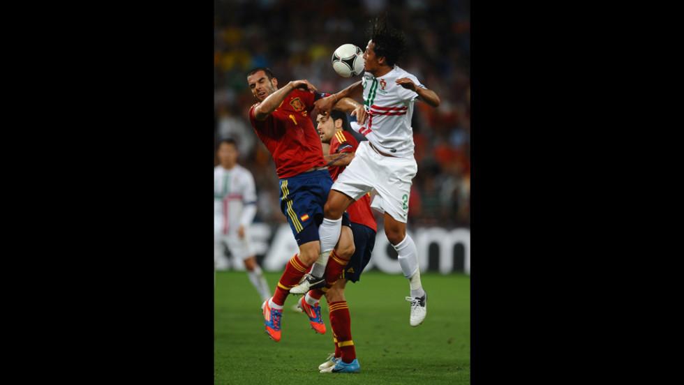 Alvaro Negredo of Spain and Bruno Alves of Portugal slam into each other.