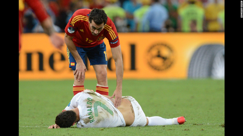 Portuguese forward Cristiano Ronaldo lies on the ground as Spanish defender Alvaro Arbeloa tries to help.