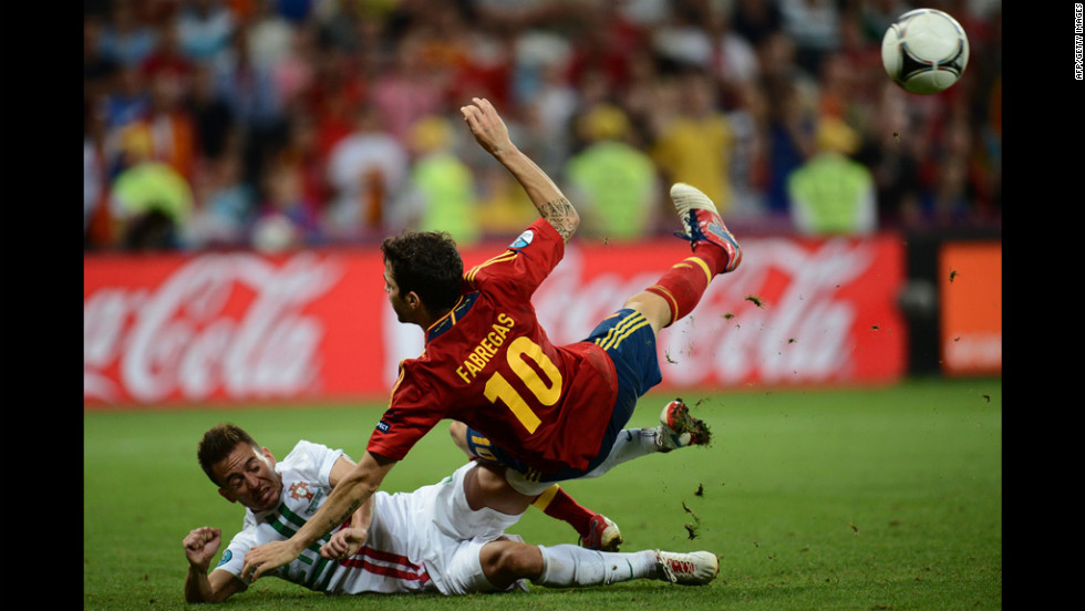 Spanish midfielder Cesc Fabregas is tackled by Portuguese defender Joao Pereira.