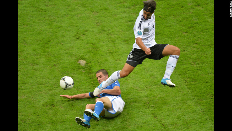 Italian defender Giorgio Chiellini slides under German midfielder Sami Khedira.