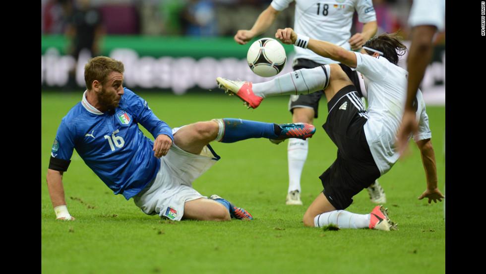 Italian midfielder Daniele De Rossi and German midfielder Mesut Ozil try to get control of the ball.