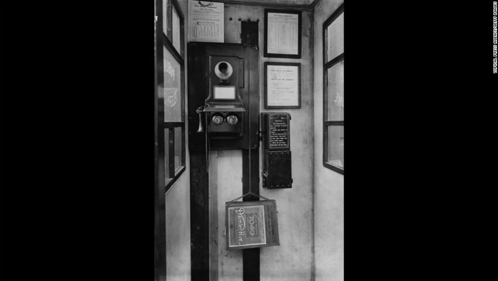 This 1924 phone booth in London features a wall-mounted phone with separate mouthpiece and receiver.