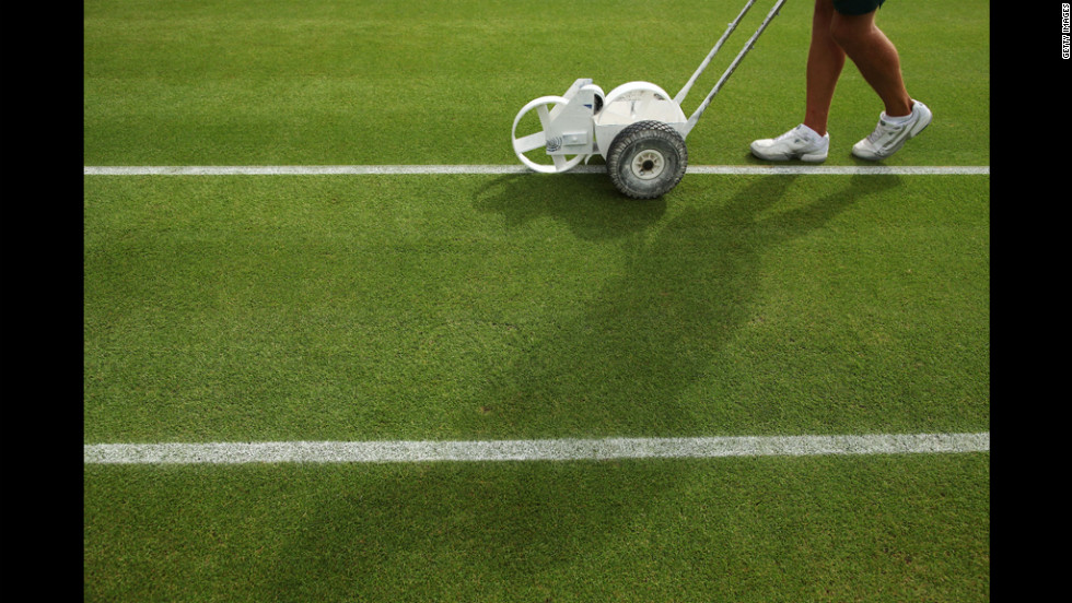Fresh lines are painted on one of the courts at Wimbledon before the beginning of the match June 28.