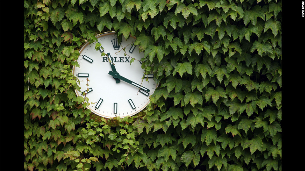 A Wimbledon tournament clock is visible through leaves Friday at the All England Lawn Tennis and Croquet Club in London.