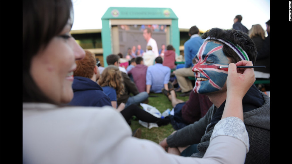 A spectator, Matt Griggs, right, has a Union Jack painted on his face by Kelsey Bennett, left, on 'Murray Mount' during the third-round men's singles match between Britain's Andy Murray and Cyprus' Marcos Baghdatis on Saturday.