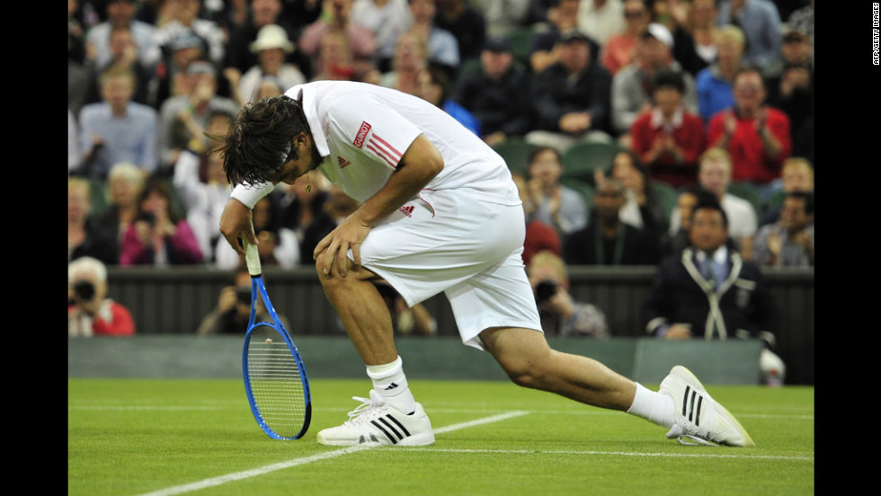 Cyprus's Marcos Baghdatis gets up after slipping during the fourth set of his third-round men's singles match against Britain's Andy Murray on Saturday.