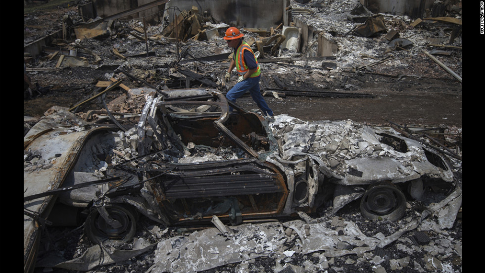 A utilities worker walks past the skeleton of a vehicle on Monday, July 2, while searching for gas leaks in a Colorado Springs community ravaged by the Waldo Canyon Fire.