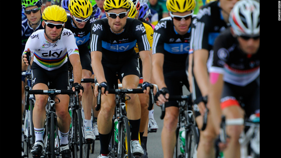 Mark Cavendish, left, rides with teammates from Britain's Team Sky, wearing yellow helmets signifying their lead in the team standings.