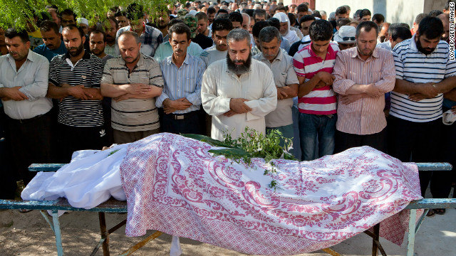 Syrians pray at the funeral of Mustafa Mahmud Badawi, 68, in Idlib province in June. A sniper killed him on his way to the dentist.