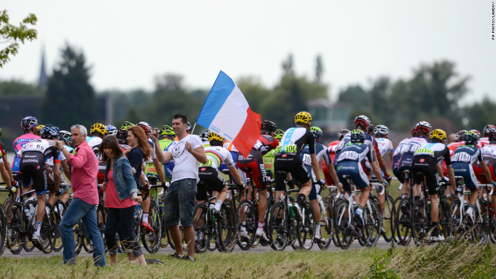 Fans wave the French flag as the peleton, led by team RadioShack-Nissan, rides past.