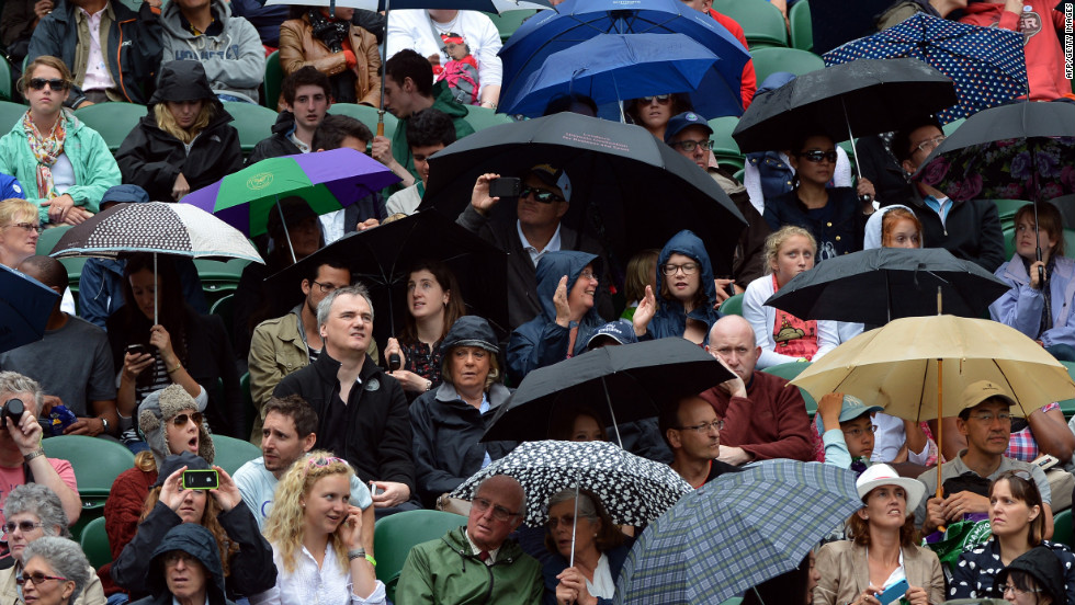 Fans at center court take shelter from the rain under umbrellas during Day Eight of the tournament on Tuesday.