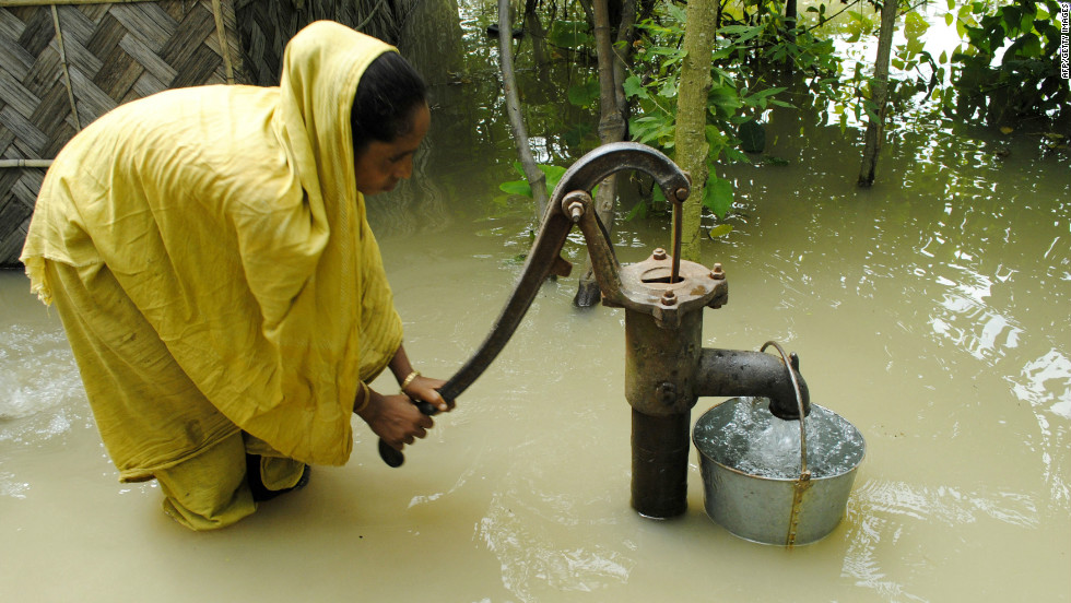 An Indian farmer pumps drinking water from a well in the floodwaters at Bulut Village on June 30. The floods have left at least 95 people dead.