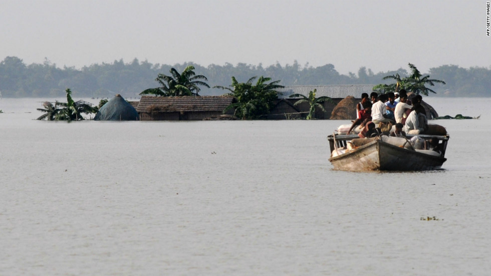 Villagers travel on a boat in the flood affected area of Jhargoan village in Morigoan district on June 29. Almost half a million peolpe are living in relief camps, Prime Minister Manmohan Singh said Monday.