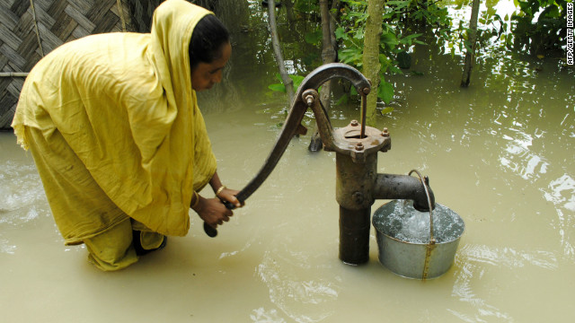 An Indian farmer pumps drinking water from well in the flood waters at Bulut Village, some 30 km away from Guwahati on June 30, 2012.