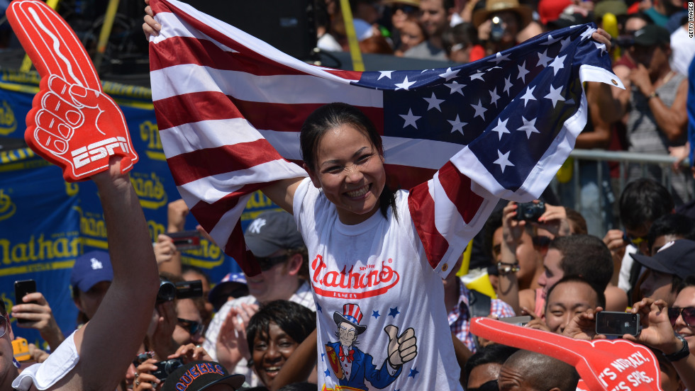"Sonya ""The Black Widow"" Thomas celebrates her victory Wednesday at Nathan's annual hot dog-eating competition in Brooklyn, New York. She set a women's world record, downing 45 hot dogs."