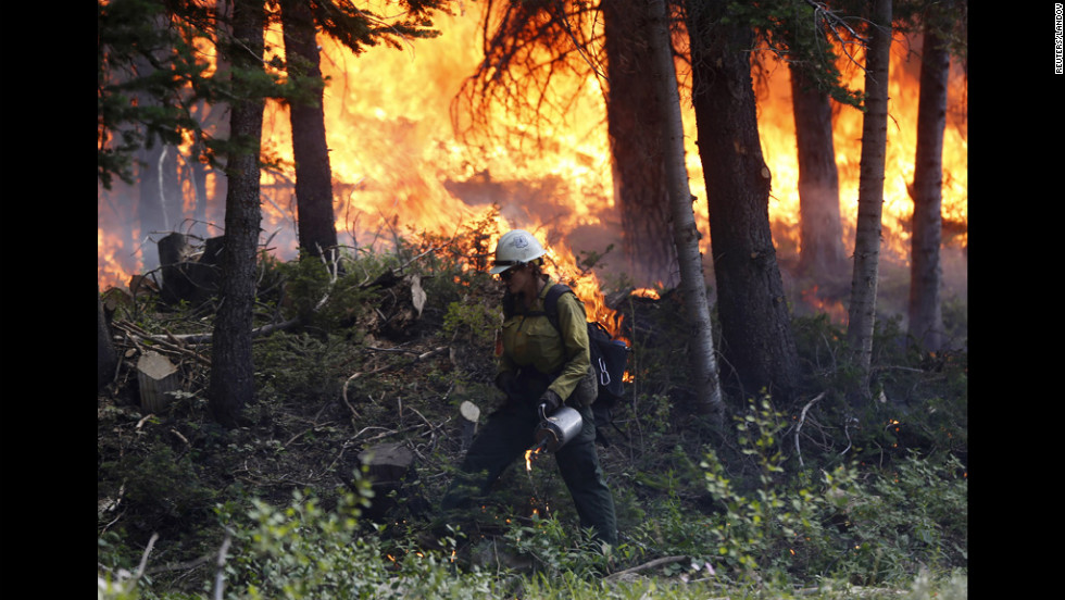 A firefighter works a burnout operation on the north flank of the Fontenelle Fire outside Big Piney, Wyoming, on Wednesday, July 4. More than 800 firefighters are working 15-hour shifts battling the fire that has exceeded 56,000 acres, according to fire information services.