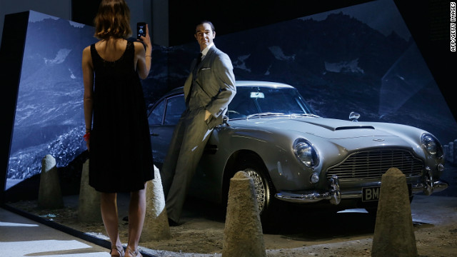 A visitor poses in front of a Sean Connery waxwork and the famous Aston Martin DB5 in July in London, England.