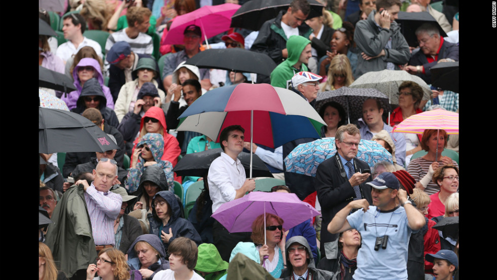 "Spectators hide under umbrellas and rain jackets as protection from the rain. <a href=""http://www.cnn.com/2012/06/26/tennis/gallery/wimbledon-best-photos/index.html"">See the best WImbledon photos.</a>"