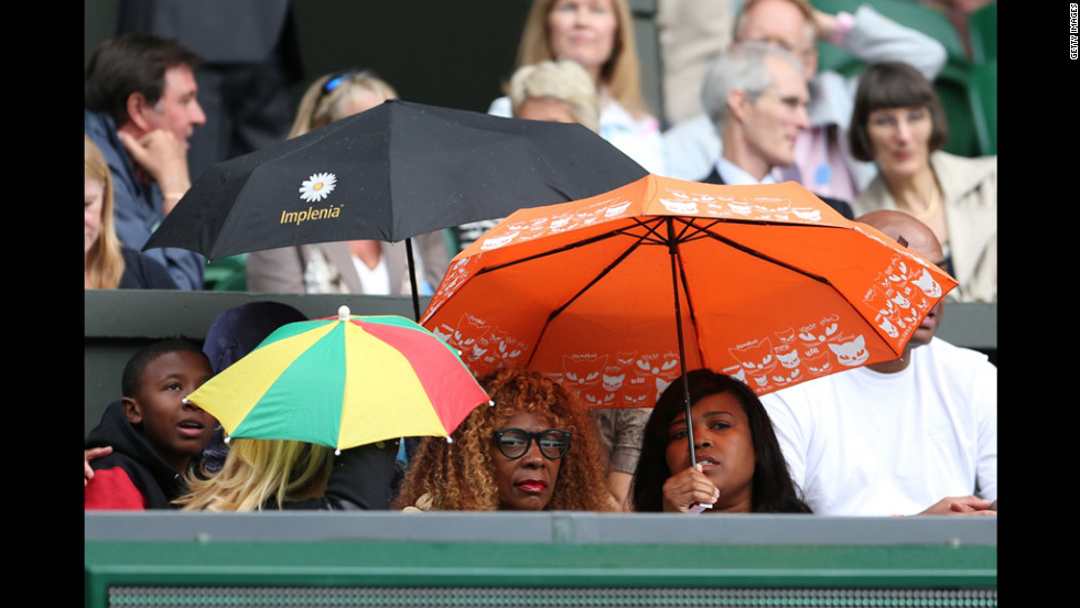 Williams' mother, Oracene Price, center, finds shelter under an umbrella during a temporary rain delay.