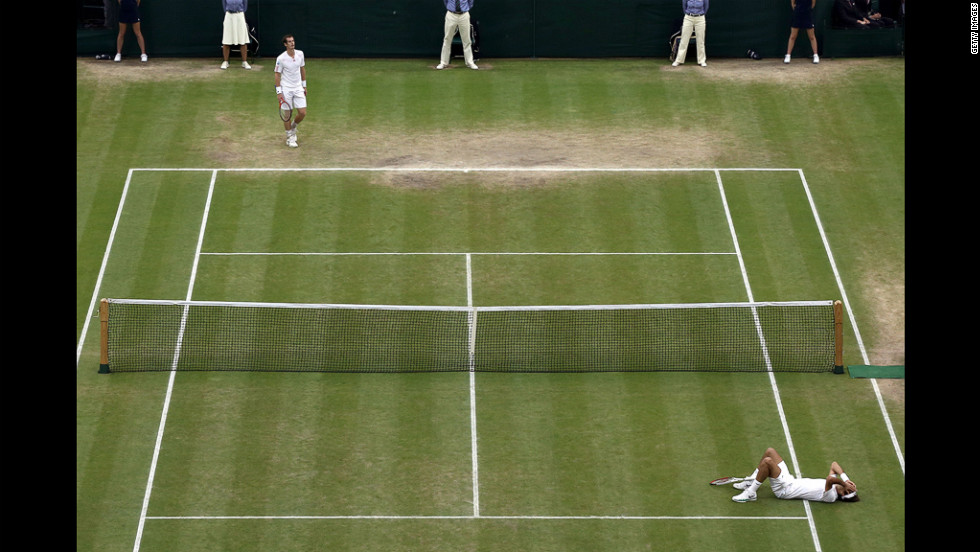 Federer lies on the grass court at the All England Tennis Club upon winning match point during the men's singles final against Murray on Sunday.