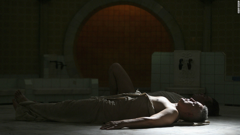 Kazak men lie down in a ray of sunlight to dry off in the Turkish section of the Arsan baths in Almaty -- a place where tradition meets the new demand for luxury.