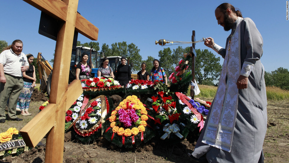 A priest conducts a funeral for Petr Ostapenko, 35, in Krymsk, Russia, on Monday, July 9. At least 171 people have been killed in flooding in the Krasnodar region since Friday.