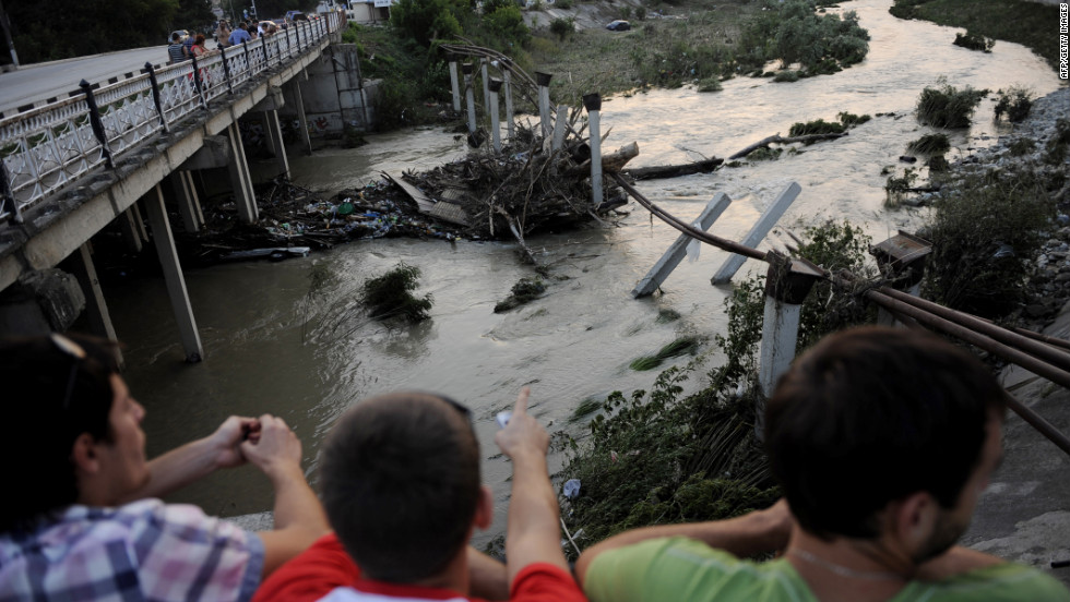 Residents look out over a river that contributed to the flooding in Krymsk on Sunday.