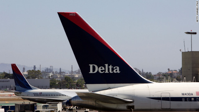 Passengers restrained a man Monday when he tried to open emergency exits shortly after landing, federal officials say.