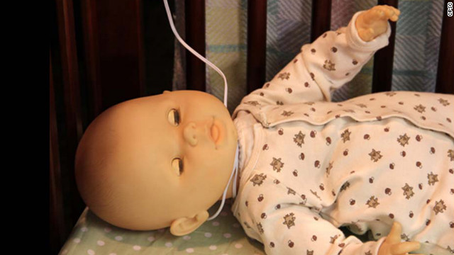 A doll is used to demonstrate how monitor cords pose a strangulation danger for babies.