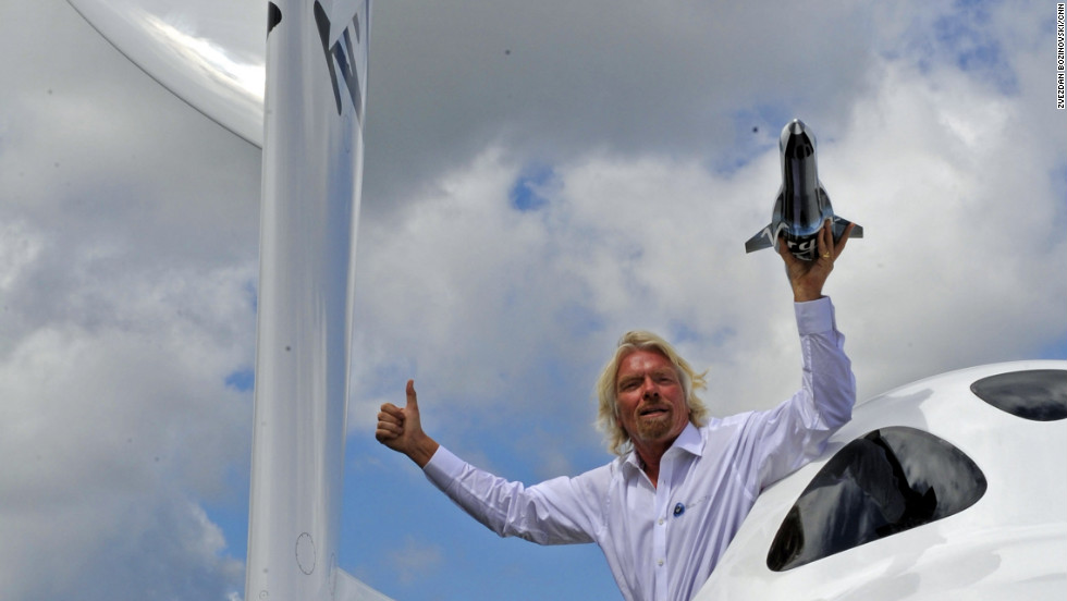 Richard Branson hangs out of the window of SpaceShipTwo, currently on display for the first time in Europe at the Farnborough Airshow, with a model of LauncherOne.  According to Branson, the maiden voyage for LauncherOne is expected to be 2015.