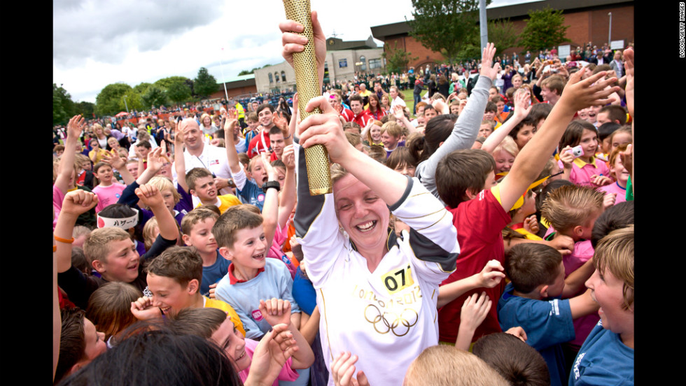 Lauren Reeder, a teaching assistant, is surrounded by local children while carrying the torch in King's Lynn, England, on July 4.