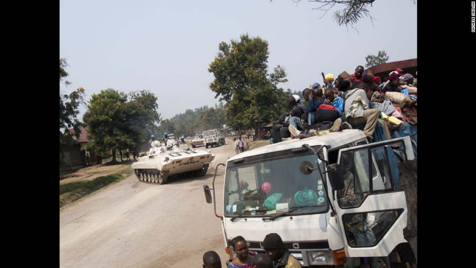 Refugees arrive en masse at the Kiwanja refugee camp as UN peacekeepers look on.