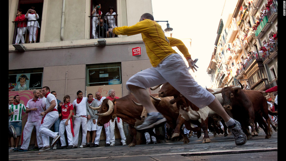 Revelers run beside Don Juan Pedro Domecq fighting bulls at Curva Estafeta on Friday.
