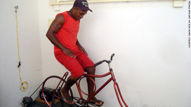 A Brazilian inmate charges a battery while pedaling a stationary bicycle.