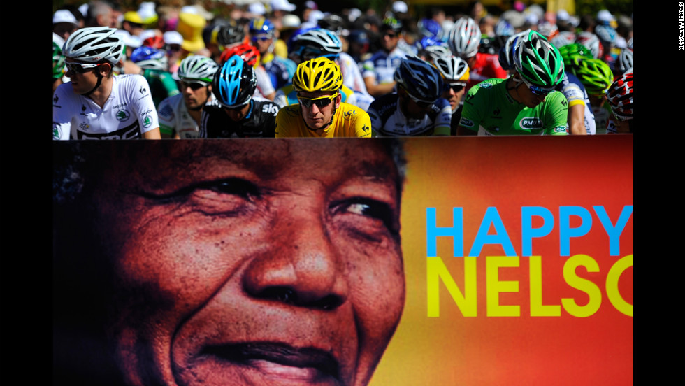 Race leader Bradley Wiggins of Great Britain, in yellow, and the main pack of riders pass a Nelson Mandela birthday banner Wednesday. People around the globe celebrated Mandela's 94th birthday.