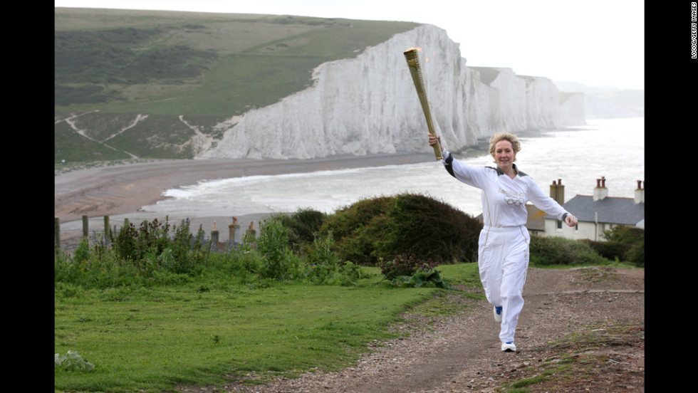 Torchbearer Kathy Gore of Uckfield runs with the Olympic flame at Seaford Head in front of the Seven Sisters cliffs in East Sussex on Tuesday, July 17.