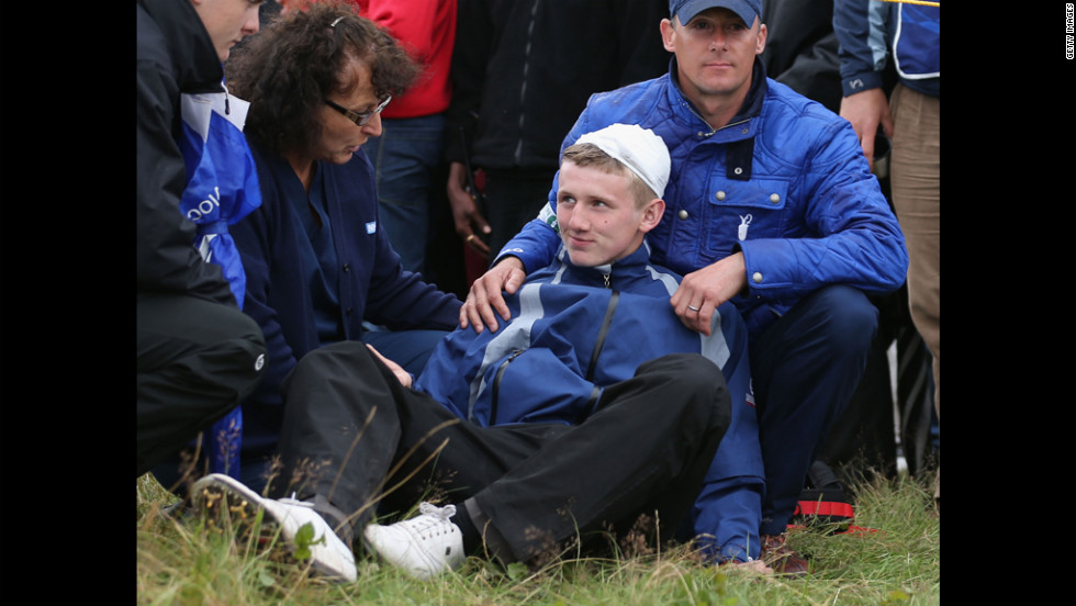 Jason Blue of Bristol gets medical attention after he was struck by Rory McIlroy's golf ball on the 15th hole on Thursday.
