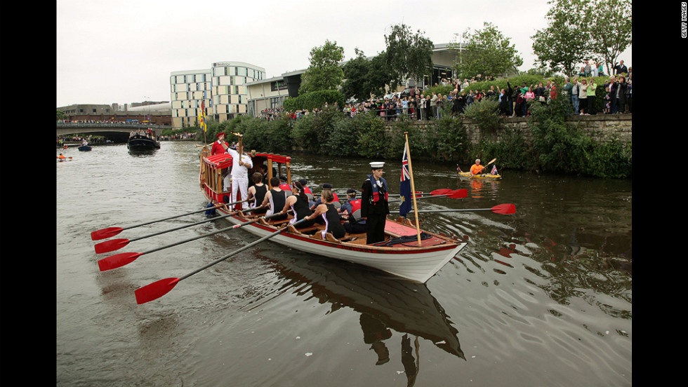 David Boyle carries the flame on a boat rowed by the Maidstone Rowing Club during his leg through Maidstone, England, on July 20.