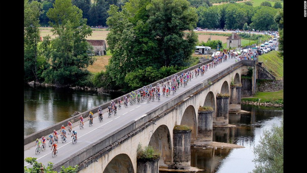 The peloton crosses La Dordogne River during Stage 18 on Friday.