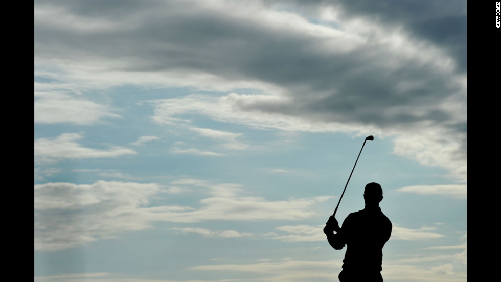 Woods takes practice swings at No. 15 under gray wisps of clouds during Friday's round.