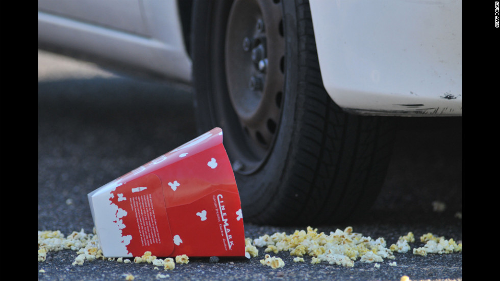 A popcorn box lies on the ground outside the Century 16 movie theater.