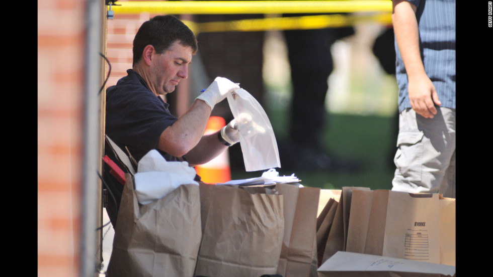 Investigators work on evidence near the apartment of James Holmes on July 20, 2012.